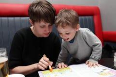 Mère et fils avec livre de coloriage Photographie stock