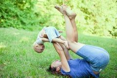 Mère et fils ayant l'amusement sur l'herbe images libres de droits