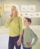 Mère et fils concernant des peintures dans les halls du musée Photographie stock