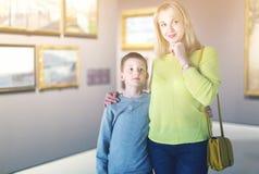Mère et fils concernant des peintures dans les halls du musée Image libre de droits