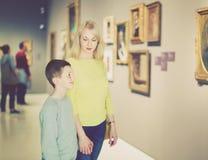 Mère et fils concernant des peintures dans les halls du musée Images libres de droits