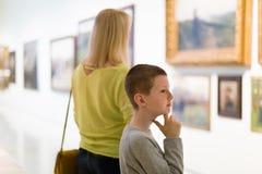 Mère et fils concernant des peintures dans les halls du musée Images stock
