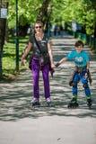 Mère et fils conduisant les patins intégrés Photo libre de droits