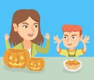 Mère et fils découpant des potirons pour Halloween illustration stock