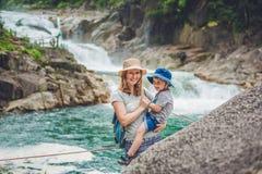 Mère et fils détendant sous une cascade Concept de vacances photos stock
