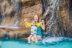 Mère et fils détendant sous une cascade dans l'aquapark photo stock