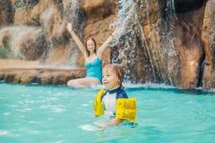 Mère et fils détendant sous une cascade dans l'aquapark photographie stock