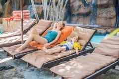 Mère et fils détendant sur les canapés du soleil par la piscine photos stock