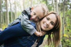 Mère et fils dans la forêt ayant l'amusement Photos stock