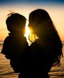 Mère et fils dans un moment profond de l'amour pendant le coucher du soleil à la plage Photographie stock libre de droits