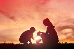 Mère et fils de silhouette plantant un arbre Photo libre de droits
