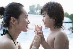 Mère et fils de sourire face à face et tenir des mains par la piscine Images stock