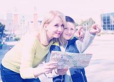 Mère et fils de sourire regardant le guide de carte Photographie stock