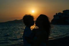 Mère et fils embrassant au coucher du soleil sur la plage Photo stock