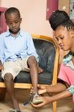 Mère et fils essayant une nouvelle chaussure photographie stock libre de droits