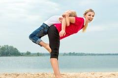 Mère et fils faisant des exercices de matin sur la plage photographie stock