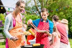 Mère et fils grillant la viande au barbecue de jardin Photos libres de droits
