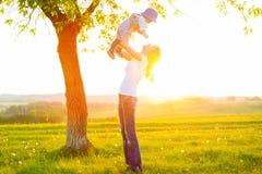 Mère et fils heureux à la lumière du soleil de coucher du soleil Image libre de droits