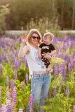 Mère et fils heureux dans le domaine de loup de floraison Photo stock