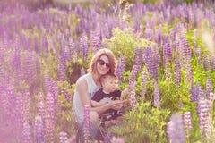 Mère et fils heureux dans le domaine de loup de floraison Photos stock