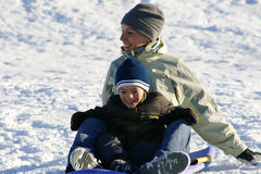 Mère et fils heureux Sledding en bas de la côte Photographie stock
