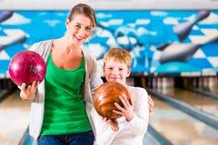 Mère et fils jouant au centre de bowling photographie stock libre de droits