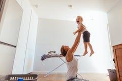 Mère et fils jouant dans la buanderie Photos stock
