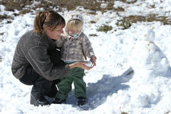 Mère et fils jouant dans la neige et bulding un bonhomme de neige images libres de droits