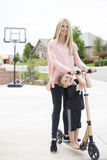 Mère et fils jouant ensemble sur un scooter dans l'allée images stock