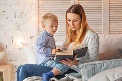 Mère et fils lisant un livre à la maison Images libres de droits