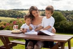 Mère et fils, lisant un livre extérieur, jour d'été photos libres de droits