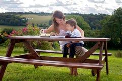Mère et fils, lisant un livre extérieur, jour d'été image stock