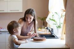 Mère et fils mangeant le tarte dans la cuisine Photo libre de droits