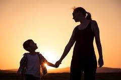 Mère et fils marchant sur le champ au temps de coucher du soleil Photos libres de droits