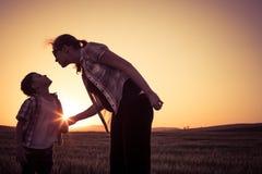 Mère et fils marchant sur le champ au temps de coucher du soleil Photos stock