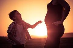 Mère et fils marchant sur le champ au temps de coucher du soleil Photo libre de droits