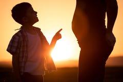 Mère et fils marchant sur le champ au temps de coucher du soleil Image libre de droits