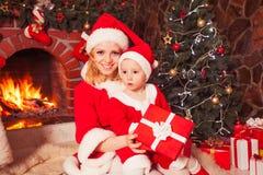 Mère et fils près de cheminée de Noël Image stock