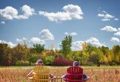 Mère et fils s'asseyant dans les chaises de jardin avec de beaux arbres de chute à l'arrière-plan Image stock