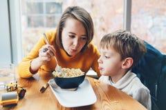 mère et fils, s'asseyant en café de restaurant à la table, alimentant mangeant des spaghetti de pâtes Photographie stock libre de droits