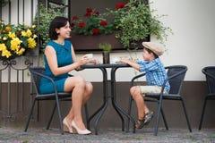 Mère et fils s'asseyant en café extérieur Images stock