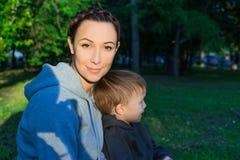Mère et fils s'asseyant sur l'herbe Image libre de droits
