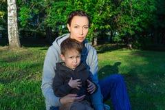 Mère et fils s'asseyant sur l'herbe en parc Images libres de droits