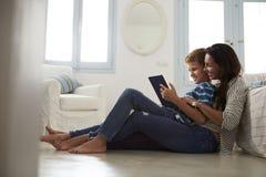 Mère et fils s'asseyant sur le plancher utilisant la Tablette de Digital Image stock