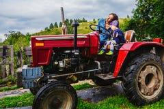 Mère et fils s'asseyant sur un tracteur Photo libre de droits