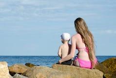 Mère et fils s'asseyant sur une roche sur le bord de la mer et examinant la distance Image libre de droits