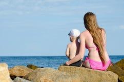 Mère et fils s'asseyant sur une roche sur le bord de la mer et examinant la distance Photos stock