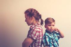 Mère et fils se tenant de nouveau au dos après querelle Photo stock