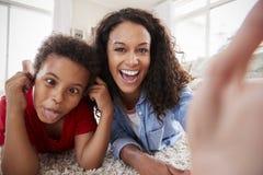 Mère et fils se trouvant sur la couverture et posant pour Selfie à la maison image stock