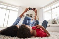 Mère et fils se trouvant sur la couverture et posant pour Selfie à la maison images stock